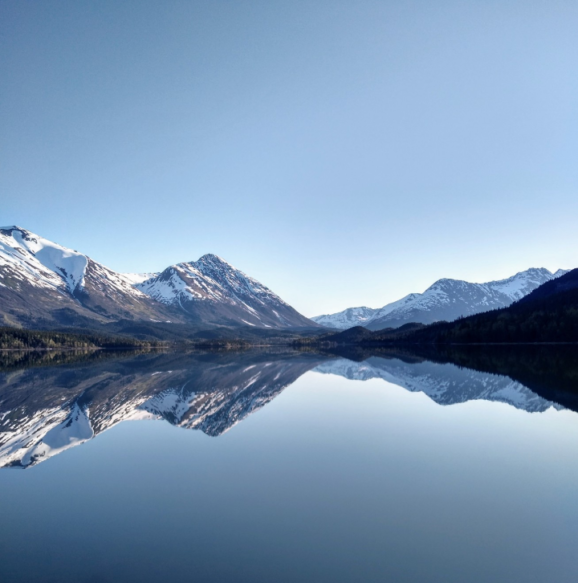 Mountains behind a lake that has a perfect reflection of the mountains
